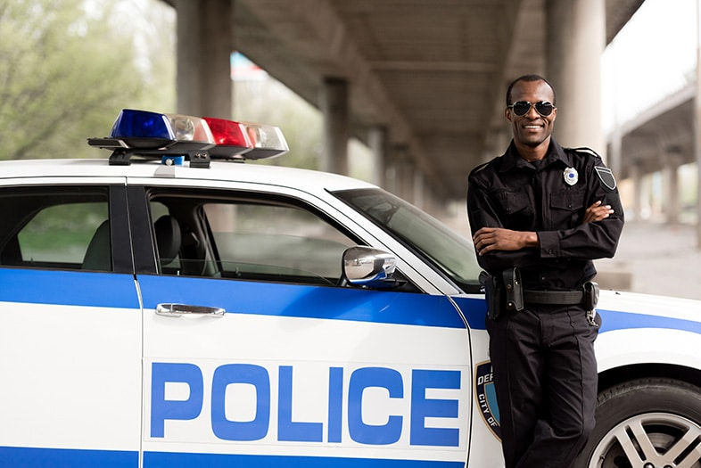 Police officer standing in front of his car; police officers are not required to wear seat belts