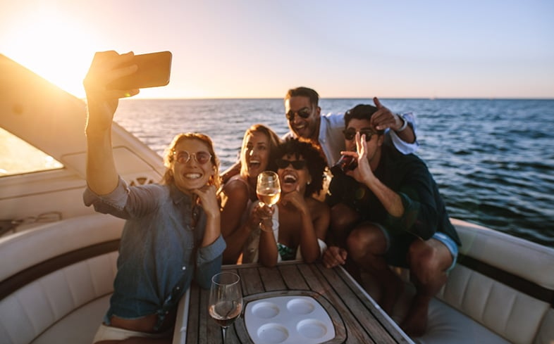 Group of friends drinking on a boat on a Wisconsin lake during the summer