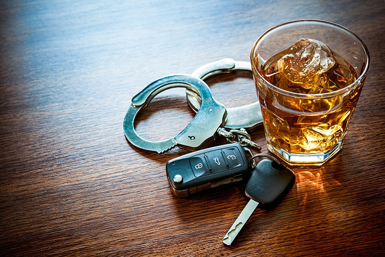 Whiskey next to car keys and handcuffs, drunk driving can lead to homicide charges
