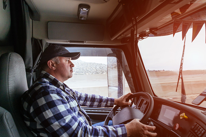Male trucker in the cabin of his vehicle with both hands on the wheel