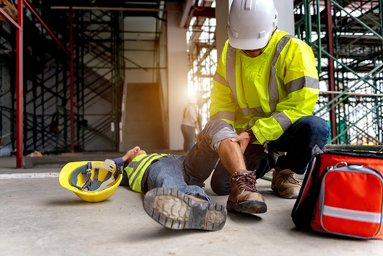 Injured construction worker being helped by a coworker after an accident