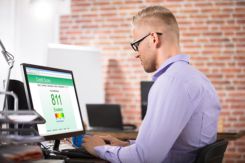 Man checking credit score on computer, surprised to see it has improved after bankruptcy