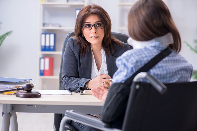 Injured employee speaking with an attorney about her denied workers' compensation claim