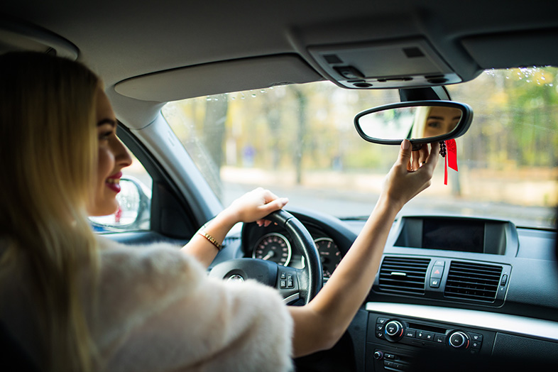 Young female driver adjusting rear-view mirror to increase her visibility