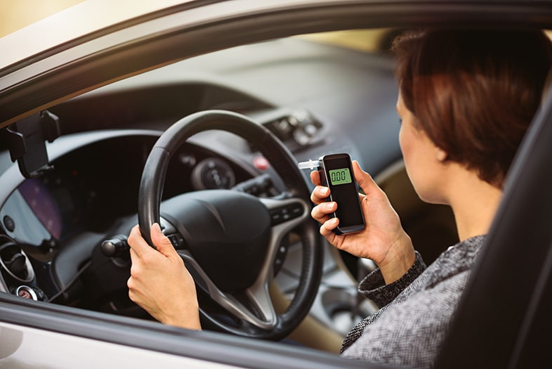 Wisconsin woman taking a breathalyzer test in the car before driving