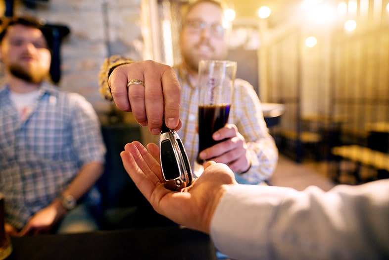 Drunk man with a beer giving his car keys to his designated driver