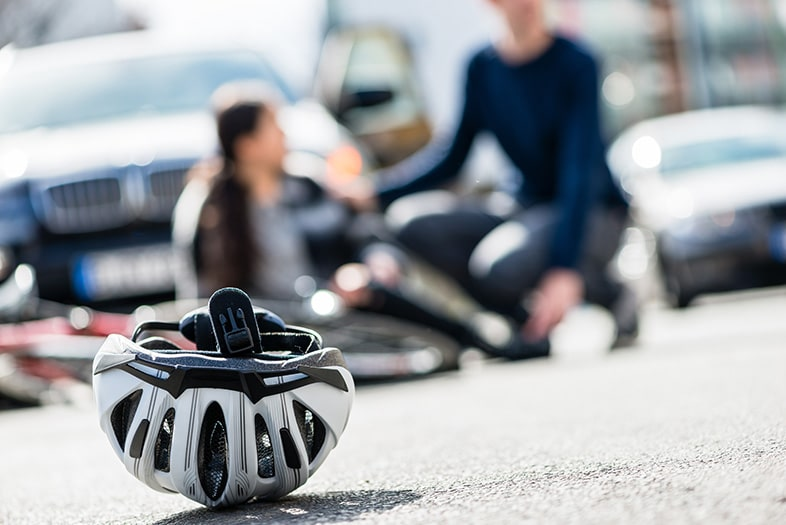 Helmet in the street after a bicycle accident in front of the driver and victim talking