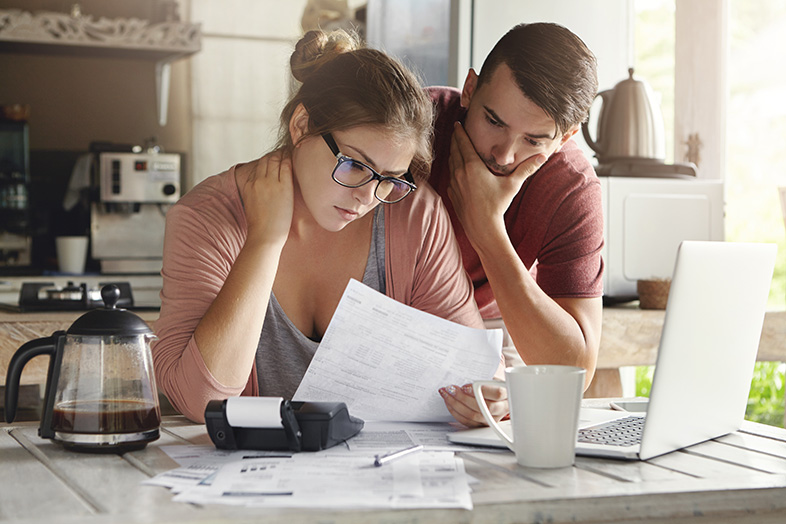Young couple examining records trying to figure out where their debt comes from
