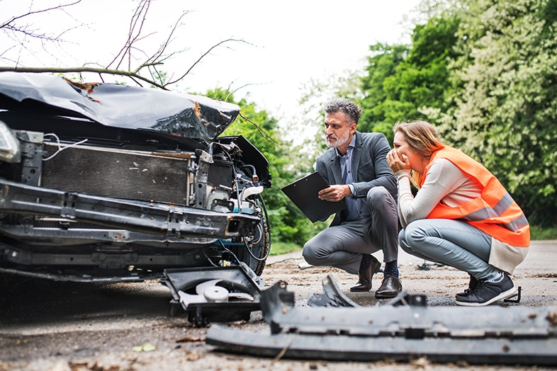 Insurance agent looking at a damaged car with the driver, explaining subrogation