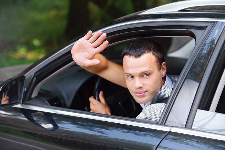 A nice, male driver waving to a another driver who let him merge