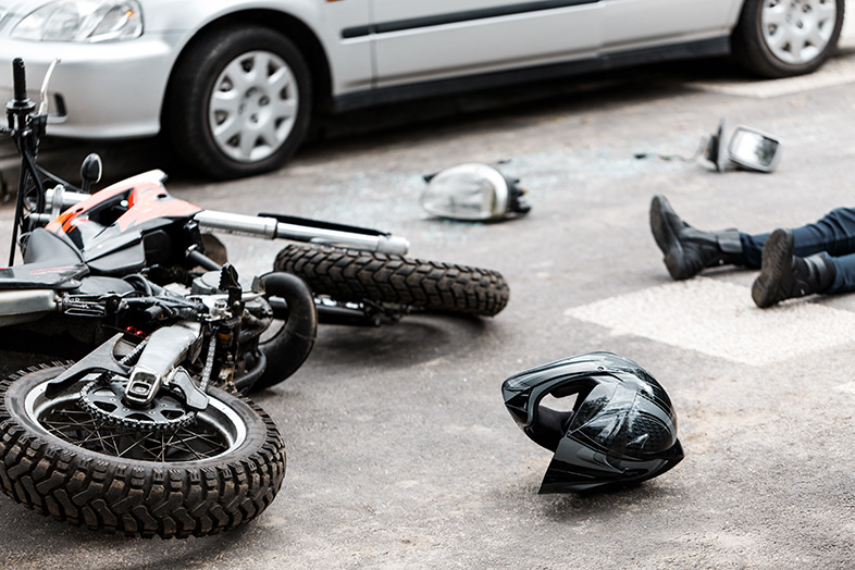 Motorcycle on the ground after an accident, victim lying nearby