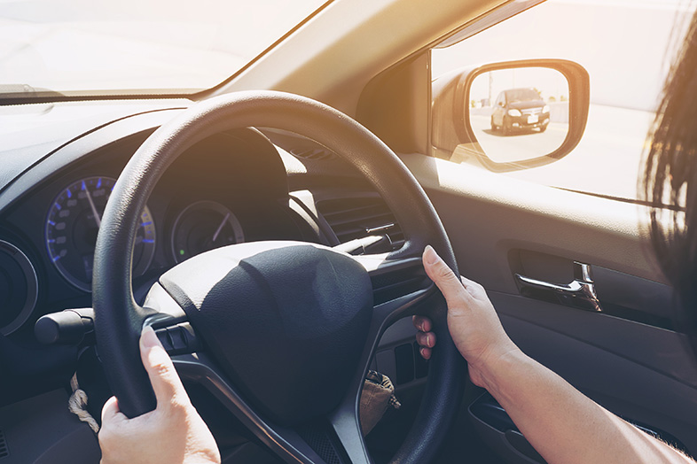 Woman driving a car with both hands on the wheel