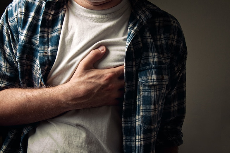 Man holding his chest because of heartburn