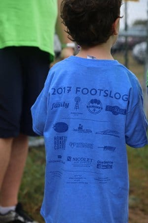 A young boy is pictured wearing a blue shirt advertising a charity event benefitting Montessori students in Eau Claire.