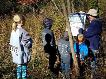 Four Montessori students listen to a man pointing at a chart give a demonstration at an outdoor charity event in Eau Claire.