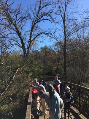 Adults and children gathered along a foot bridge pose for a picture at an outdoor charity event for Montessori students.