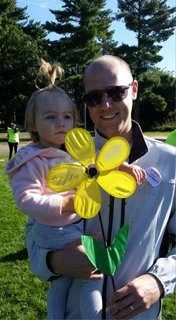 Personal injury attorney Adam Nicolet smiles while holding his daughter Avarie who poses with a decorative yellow flower.